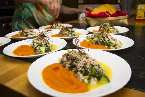 Plates of fresh ceviche and sauce on a table with the chef.