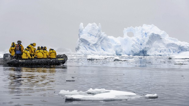 Group of passengers from a small ship cruise expedition in Antarctica passing by glaciers on a skiff excursion.