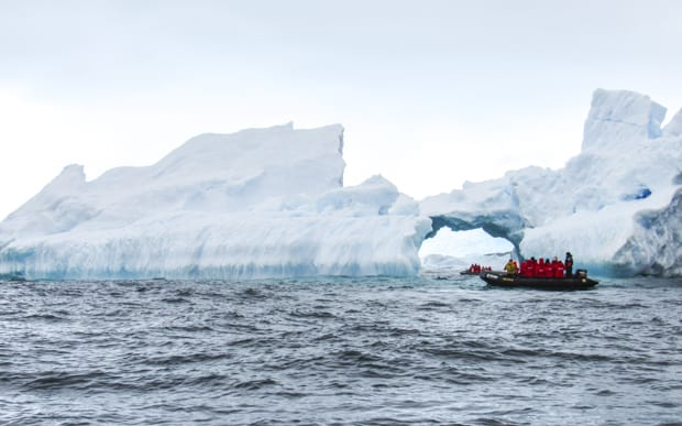 Passengers on a skiff excursion from a small ship cruise ride up close to large icebergs.