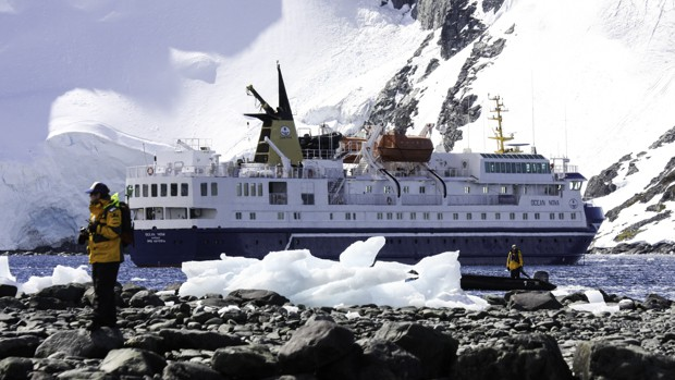 Exterior of a small expedition cruise ship close to land in Antarctica with people walking on land in front.