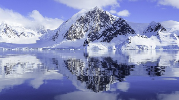 Bright blue sky and reflections of the mountains in Antarctica as seen from a small ship cruise.