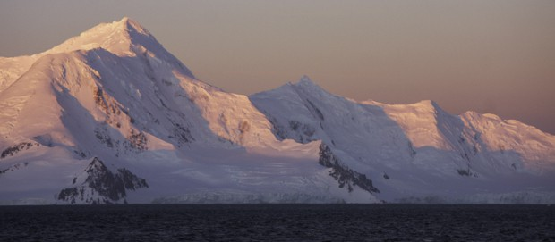 Sunset in Antarctica leaving the landscape pink as seen from a small ship cruise.