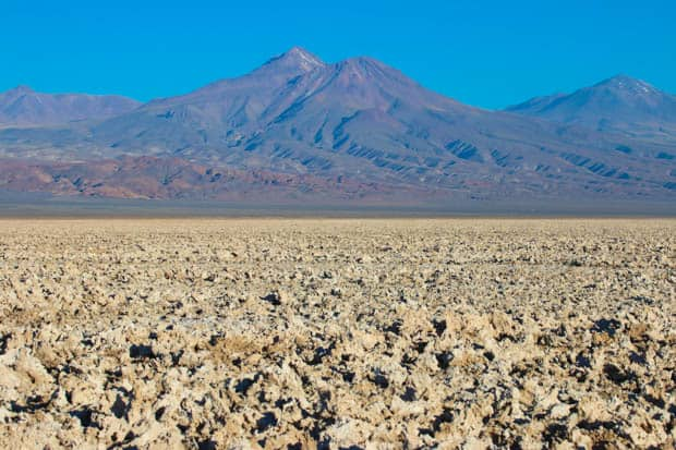 A desert view of rough ground with mountains in the background.