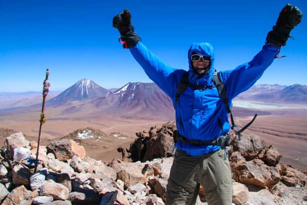 Author on the top of a mountain with arms in the air in celebration of summitting with mountains and plains in the background.