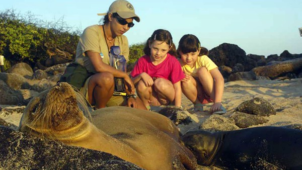 Young girls with a guide looking at sleeping Galapagos sea lions on a beach.