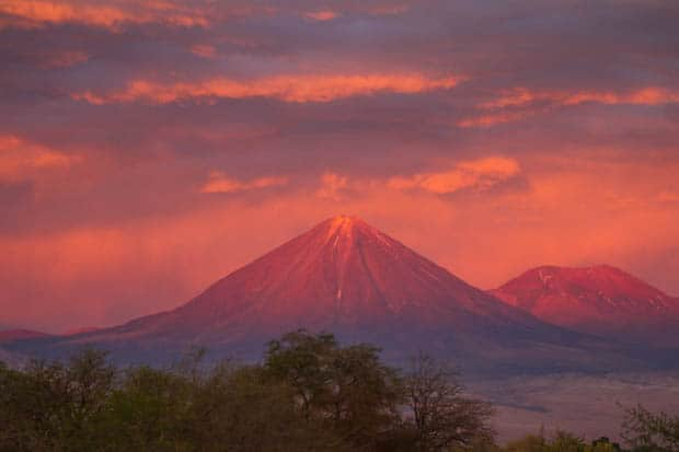 A volcano with the sun setting on the peak creating a pink sky and pink mountains in Atacama, Chile