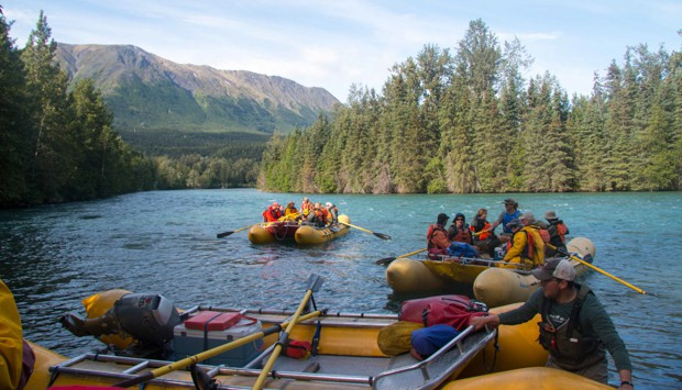 A group of people in rafts floating down the Kenai River.
