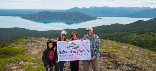 A family holding a flag above at the top of a hill in Alaska.