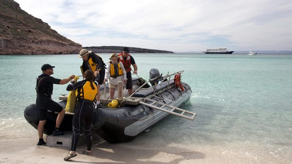 people getting off of a zodiac on shore in baja