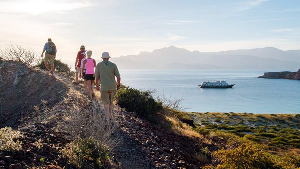 group of people hiking on a land tour with a small ship in the background