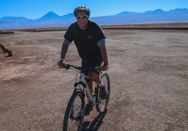 A Chile traveler riding a mountain bike over the desert and smiling.