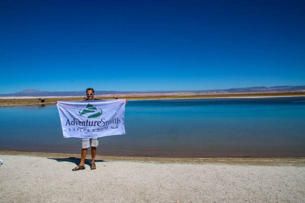 Author standing with AdventureSmith flag in front of a salt lake in the Atacama Desert in Chile.