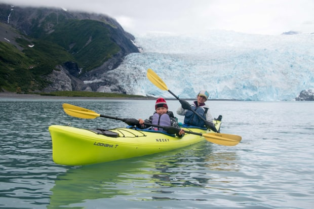 A mom and son kayaking near a glacier in Alaska.