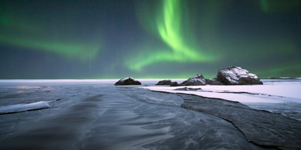 Aurora Borealis northern lights at night above the snow in the Arctic