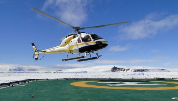 Helicopter taking off from the landing pad aboard their small expedition ship in Antarctica.