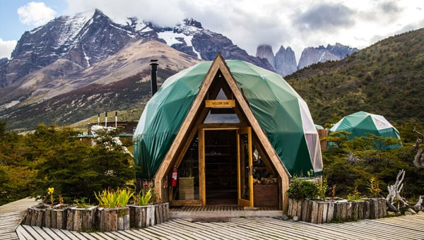 Dome adventure lodge in Patagonia with green roof and A-frame entrance
