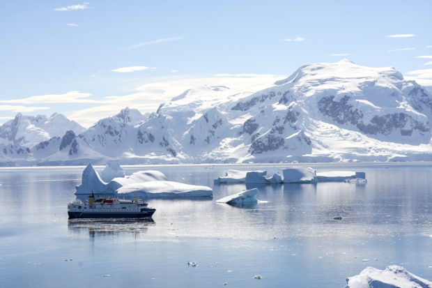 Small expedition cruise ship surrounded by the beautiful white landscape in Antarctica.