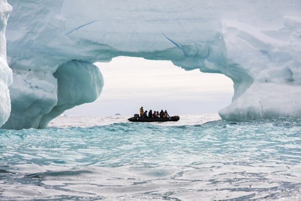 Guests on a skiff excursion in the middle of a large arc of an iceberg in Antarctica.