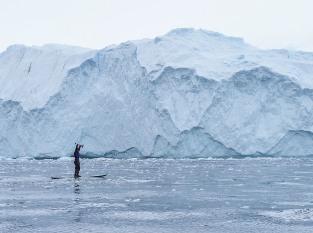 Guest from a small cruise ship stand up paddle boarding in Antarctica close to the ice shelf and with ice floating in the water.