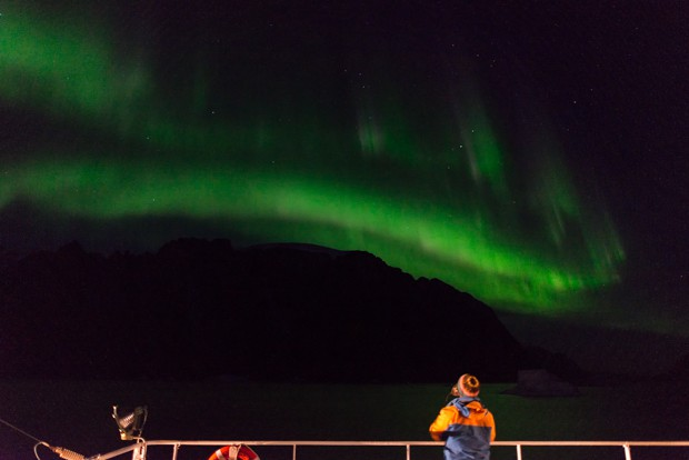 A traveler looks up at the Aurora Borealis on an Arctic small ship cruise trip