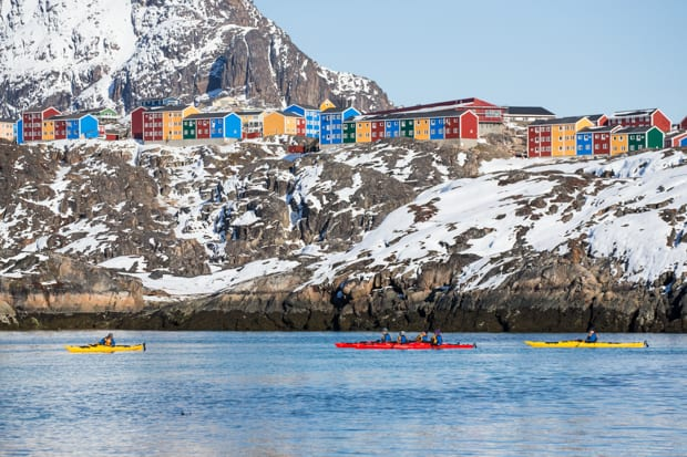 People kayaking in front of a colorful Arctic village