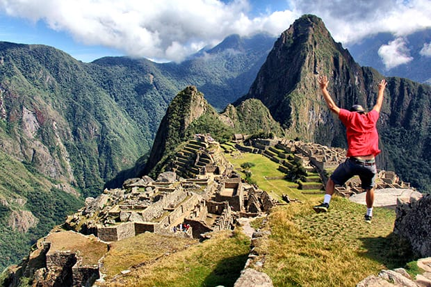 Person jumping in excitement while hiking Machu Picchu on a land tour.