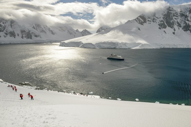 Group snowshoeing uphill in Antarctica with their small ship in the background.