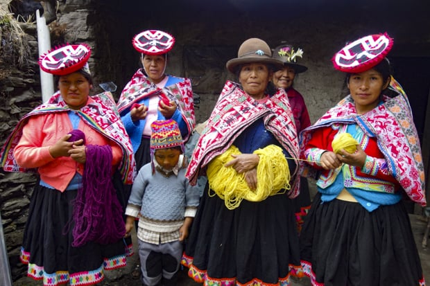 A group of Peruvian women in their colorful traditional clothes carrying yarn.