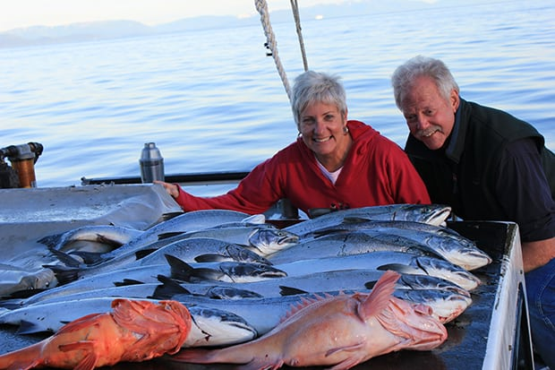 A happy couple posing on their small ship cruise in Alaska with more than 10 large locally caught fresh fish and salmon on a table.