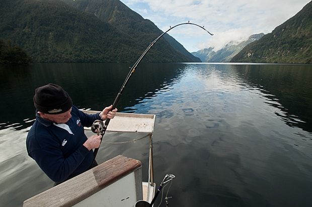 A man fishing from a small ship in a serene channel in New Zealand
