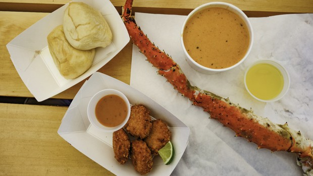 A meal of Alaskan king crab, soup and fried fish on a table.
