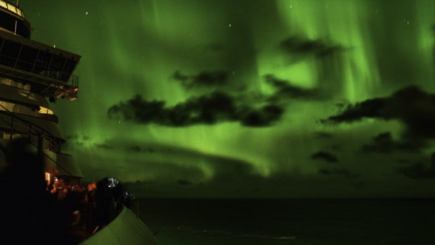Green northern lights in the night sky viewed from the deck of a Alaskan small ship cruise.