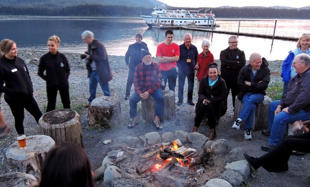 Guests at Orca Point Lodge in Alaska sitting around a campfire on the beach with their small ship in the background.