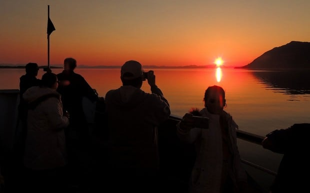 Guests on the bow of their small ship cruise in Alaska taking a picture of the orange sunset.
