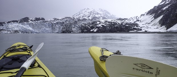 Two kayaks resting in the ocean looking at tidewater glaciers in Alaska.