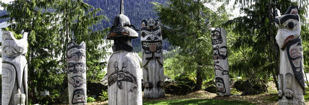 Tlingit totem poles set in a circle among the Alaskan forest.