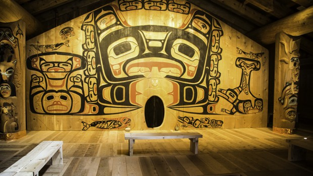 A Tlingit house with large totem art on the walls and poles.