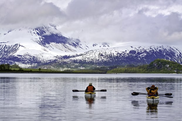 Two Alaskan travelers relaxing in kayaks while observing snowy mountains.