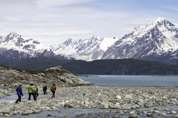 Group of Alaskan travelers hiking on a rocky shoreline with snowy mountains and small ship cruise in the background.