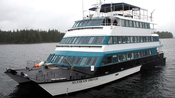 An Alaska small ship, the white and teal, Alaskan Dream, floats in the inside passage on an Alaska cruise.