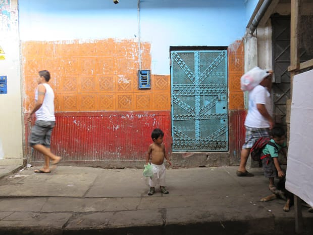 A small boy standing on a side walk in Peru front of bright colored wall.