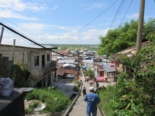 People walking down a stairway with old worn down buildings and houses an either side.