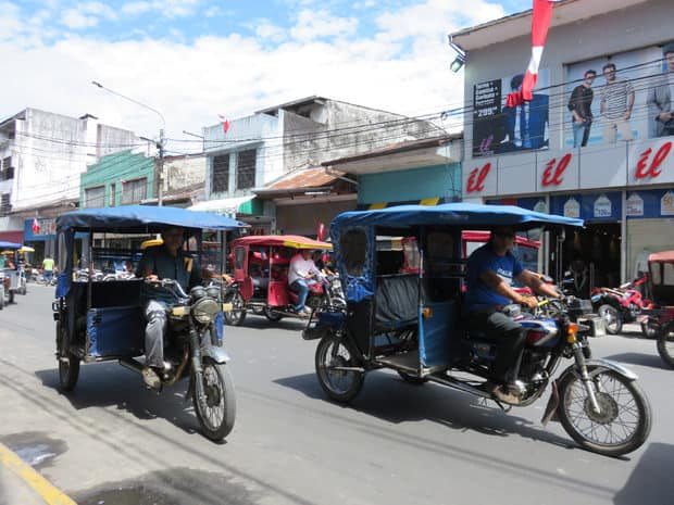 A busy street filled with mototaxi's driving by in Peru.