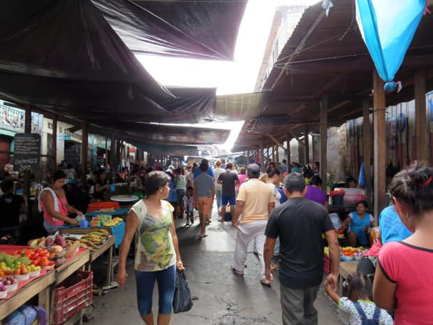A busy market place in Peru filled with vendors and customers.