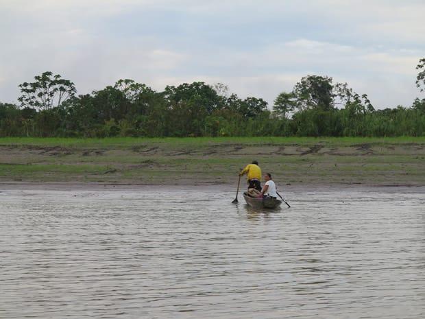 Fisherman in a canoe in the Peruvian Amazon river.