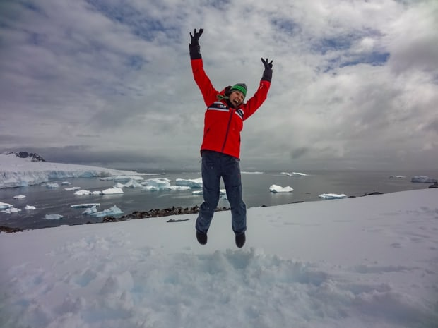 Happy guest from a small ship cruise stepping foot on land in Antarctica and jumping with her arms up.