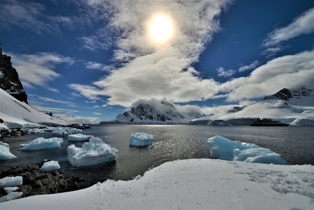 Sun behind clouds with mountains and icebergs in Antarctica.