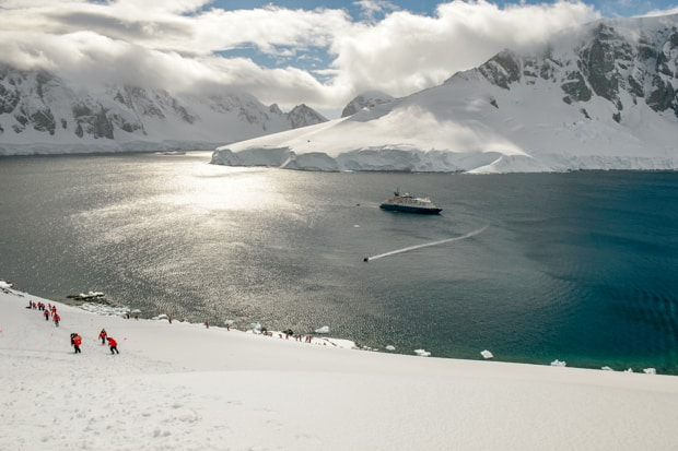 Guests hiking on snow with their small ship in the background in Antarctica.