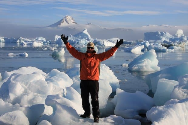 Small ship cruise guest posing with many icebergs behind him while on land tour in Antarctica from small ship cruise.
