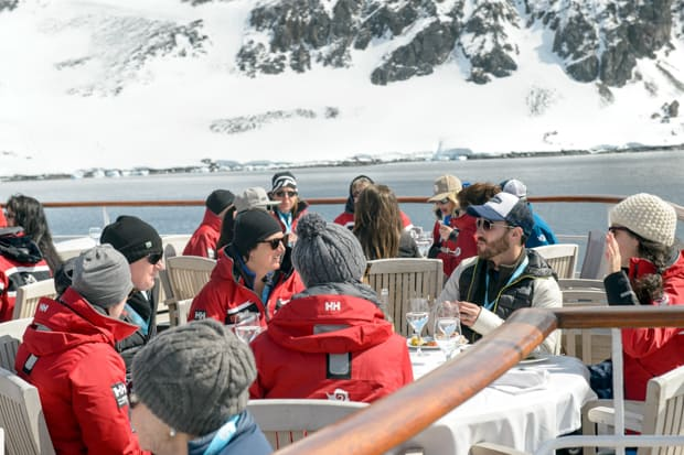 Guests aboard a small ship cruise in Antarctica enjoying the sun, food, and drink on the deck.